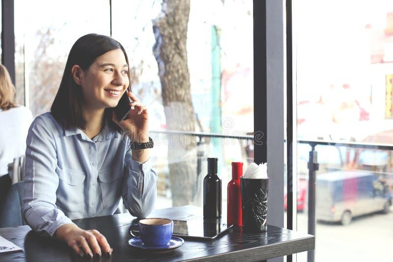 Ευτυχή νέα cappuccino κατανάλωσης γυναικών, latte, macchiato, τσάι, χρησιμοποιώντας τον υπολογιστή ταμπλετών και μιλώντας στο τηλ στοκ φωτογραφία με δικαίωμα ελεύθερης χρήσης
