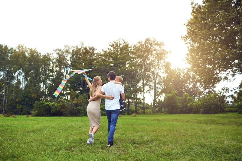 Ευτυχή οικογενειακά τρεξίματα με έναν ικτίνο μέσω της χλόης στο πάρκο στοκ εικόνες