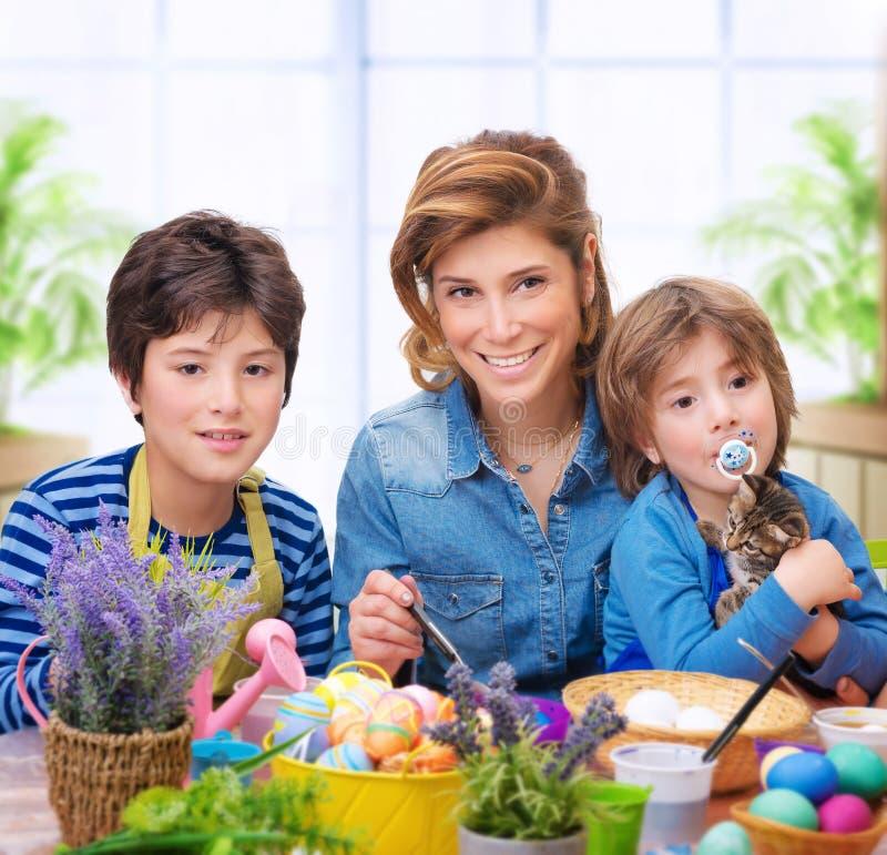 Ευτυχή οικογενειακά χρωματίζοντας αυγά στοκ εικόνα