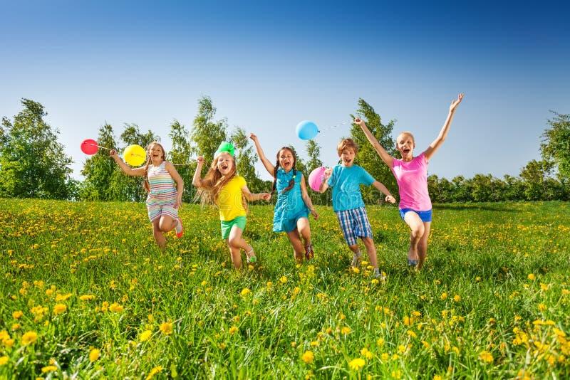 Ευτυχή πέντε παιδιά με τα μπαλόνια που οργανώνονται στον τομέα στοκ εικόνα