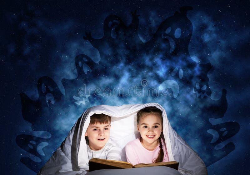 Ευτυχή παιδάκια που διαβάζουν το βιβλίο στο κρεβάτι στοκ φωτογραφίες με δικαίωμα ελεύθερης χρήσης