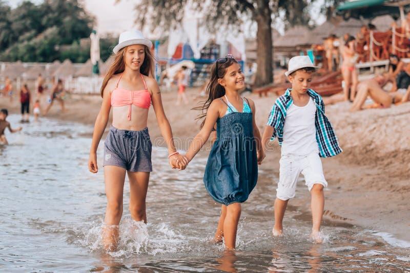 Ευτυχή παιδιά που περπατούν μαζί κατά μήκος της ακτής και που κρατούν τα χέρια στοκ φωτογραφία