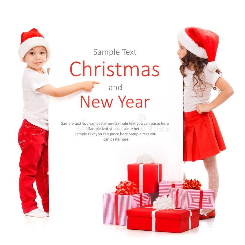 Ευτυχή παιδάκια στο καπέλο Santa που κρυφοκοιτάζουν από πίσω στοκ εικόνες