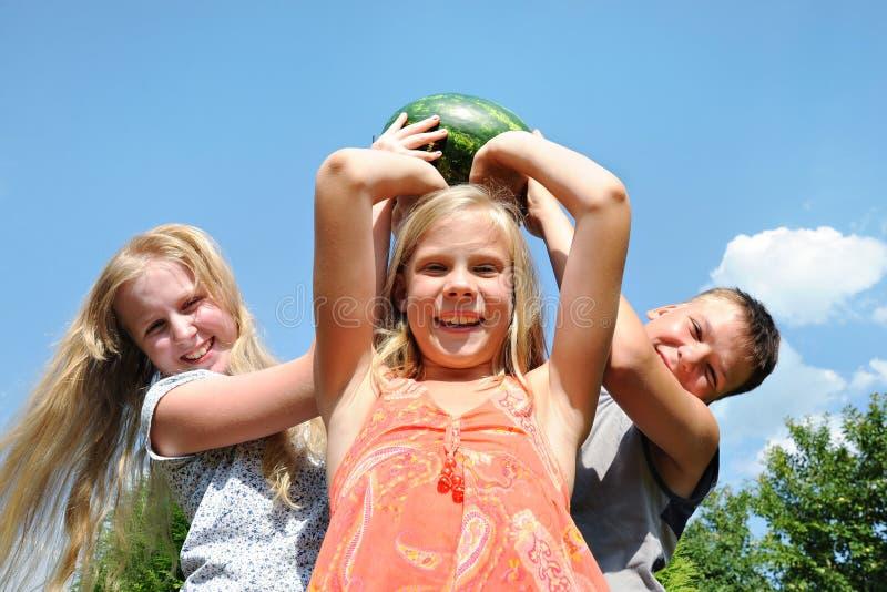 Ευτυχή παιδιά με ένα μεγάλο καρπούζι στοκ εικόνες