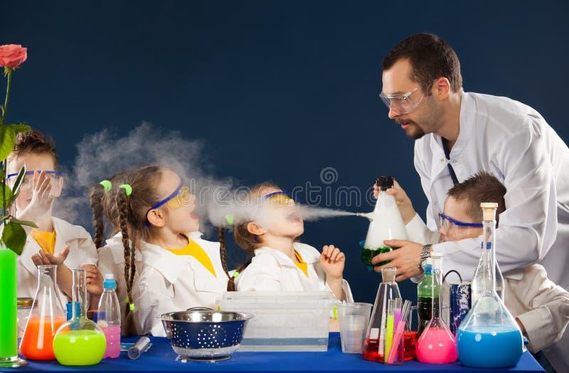 Ευτυχή παιδιά με τον επιστήμονα που κάνει τα πειράματα επιστήμης στο εργαστήριο στοκ εικόνα