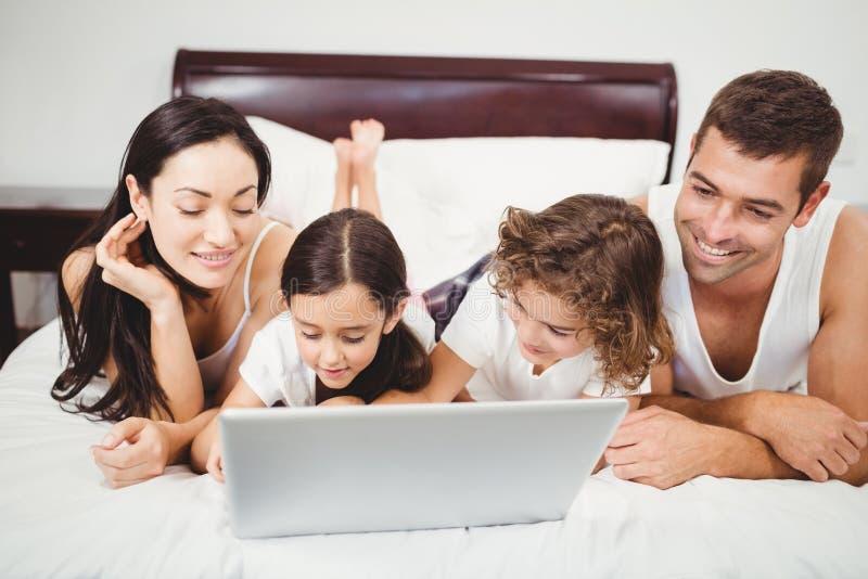 Ευτυχή παιδιά με τους γονείς που χρησιμοποιούν το lap-top στο κρεβάτι στοκ εικόνες με δικαίωμα ελεύθερης χρήσης