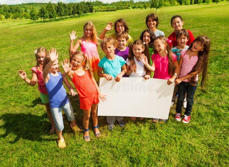 Ευτυχή παιδιά με το έμβλημα στοκ εικόνες