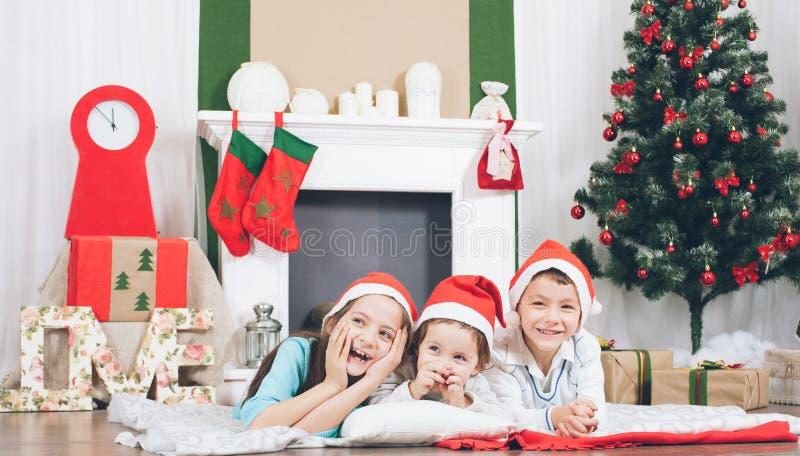 Ευτυχή παιδιά που γελούν και που χαμογελούν στο υπόβαθρο του χριστουγεννιάτικου δέντρου και της εστίας στοκ εικόνες