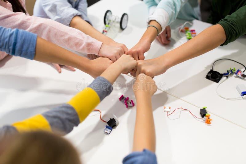 Ευτυχή παιδιά που κάνουν την πρόσκρουση πυγμών στο σχολείο ρομποτικής στοκ εικόνες