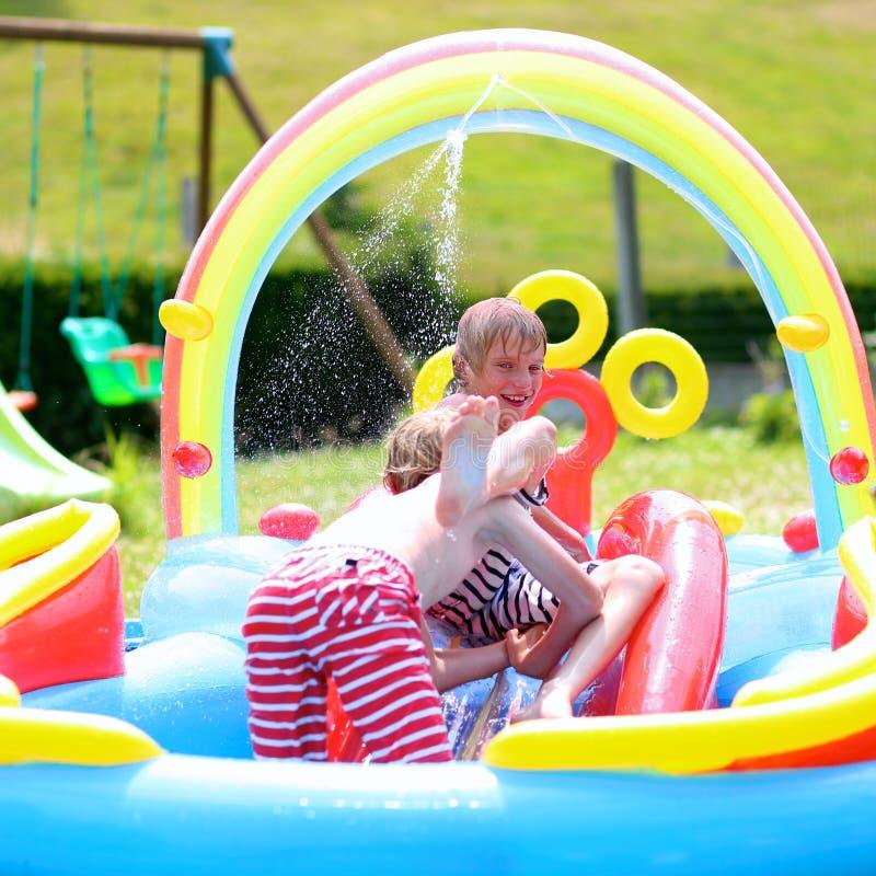 Ευτυχή παιδιά που καταβρέχουν στη διογκώσιμη λίμνη κήπων στοκ εικόνες με δικαίωμα ελεύθερης χρήσης
