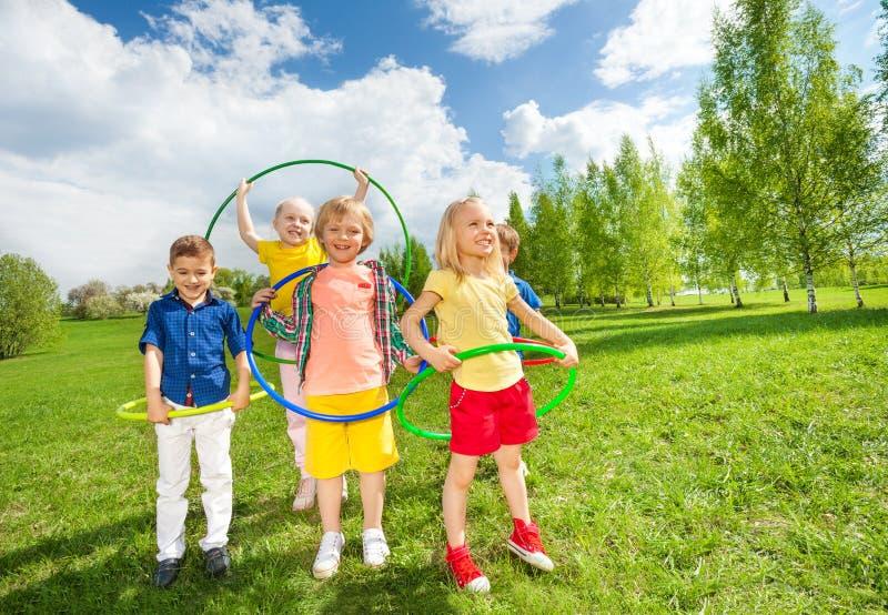 Ευτυχή παιδιά που κρατούν τις στεφάνες hula κατά τη διάρκεια των ασκήσεων στοκ εικόνα με δικαίωμα ελεύθερης χρήσης