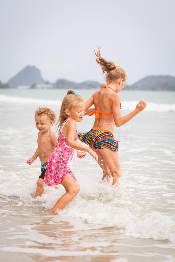 Ευτυχή παιδιά που παίζουν στην παραλία στοκ εικόνα