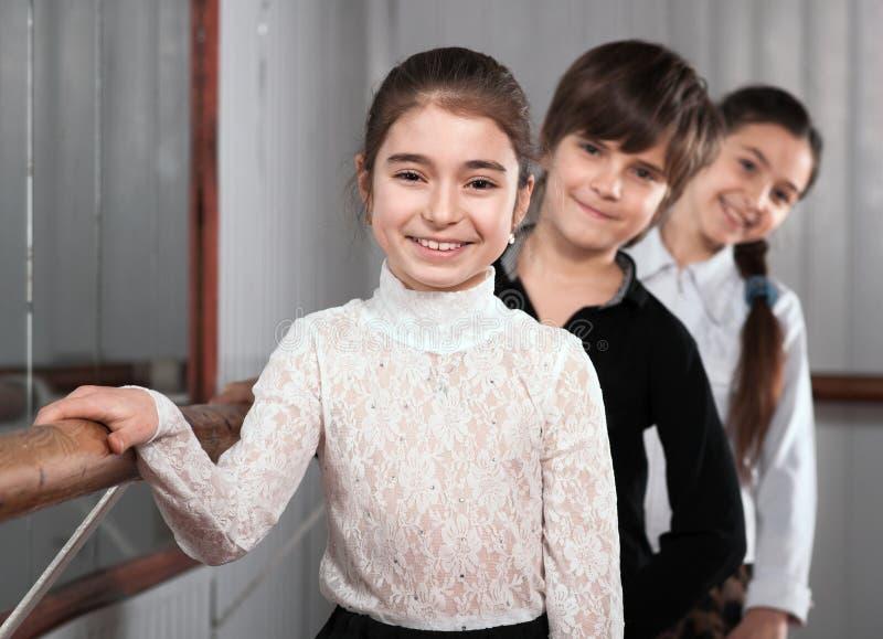 Παιδιά που στέκονται κοντά σε μια μπάρα μπαλέτου στοκ φωτογραφίες