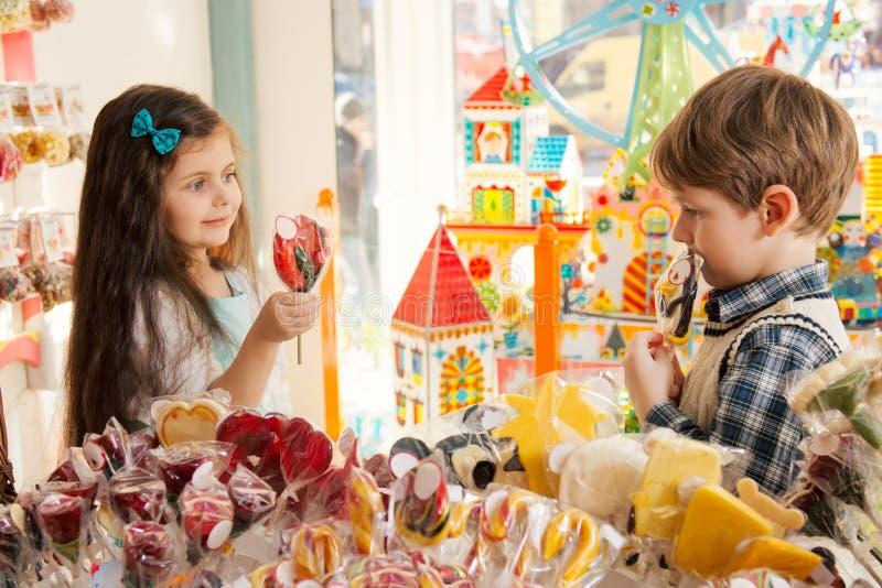 Ευτυχή παιδιά σε ένα κατάστημα καραμελών στοκ εικόνες