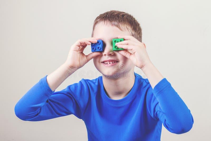 Ευτυχή παιδικά παιχνίδια με τους ζωηρόχρωμους πλαστικούς φραγμούς παιχνιδιών στοκ φωτογραφίες