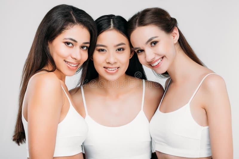 ευτυχή πολυπολιτισμικά κορίτσια που θέτουν στους άσπρους στηθοδέσμους στοκ φωτογραφία με δικαίωμα ελεύθερης χρήσης