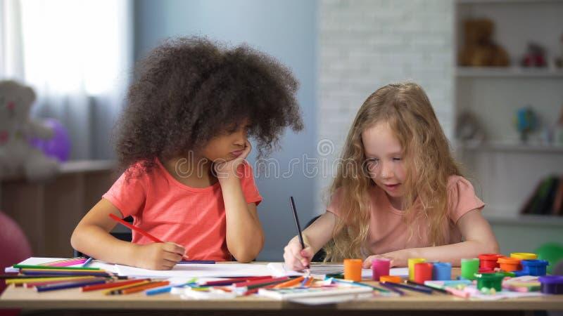 Ευτυχή προσχολικά πολυφυλετικά παιδιά που σύρουν στον πίνακα με τα ζωηρόχρωμα μολύβια στοκ φωτογραφίες