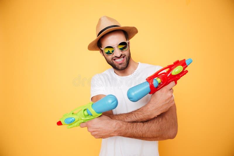 Ευτυχή πυροβόλα όπλα νερού παιχνιδιών εκμετάλλευσης νεαρών άνδρων στοκ φωτογραφίες