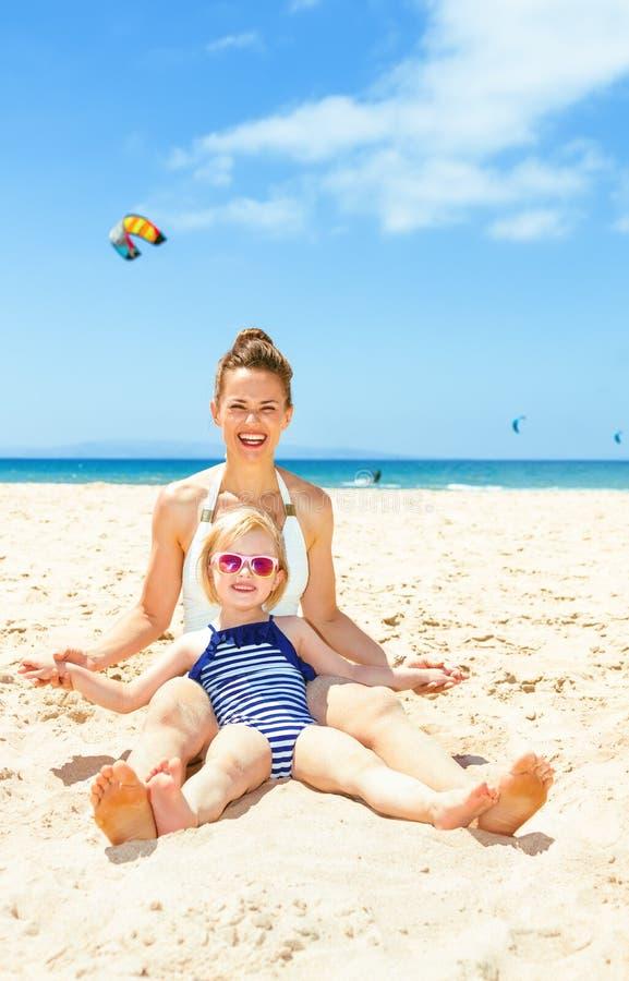 Ευτυχή σύγχρονα μητέρα και παιδί στη beachwear συνεδρίαση στην ακτή στοκ φωτογραφίες με δικαίωμα ελεύθερης χρήσης