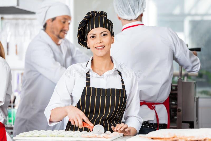 Ευτυχή τέμνοντα Ravioli αρχιμαγείρων ζυμαρικά με τους συναδέλφους στοκ φωτογραφίες