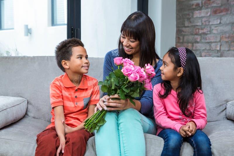 Ευτυχή τριαντάφυλλα εκμετάλλευσης μητέρων που κάθονται με το γιο και την κόρη της στον καναπέ στοκ φωτογραφίες με δικαίωμα ελεύθερης χρήσης