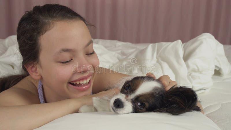 Ευτυχή φιλιά και παιχνίδια κοριτσιών εφήβων με το σκυλί Papillon στο κρεβάτι στοκ φωτογραφίες με δικαίωμα ελεύθερης χρήσης