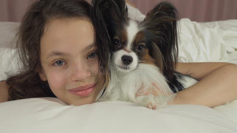 Ευτυχή φιλιά και παιχνίδια κοριτσιών εφήβων με το σκυλί Papillon στο κρεβάτι στοκ φωτογραφία με δικαίωμα ελεύθερης χρήσης