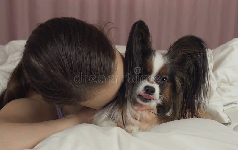 Ευτυχή φιλιά και παιχνίδια κοριτσιών εφήβων με το σκυλί Papillon στο κρεβάτι στοκ εικόνες