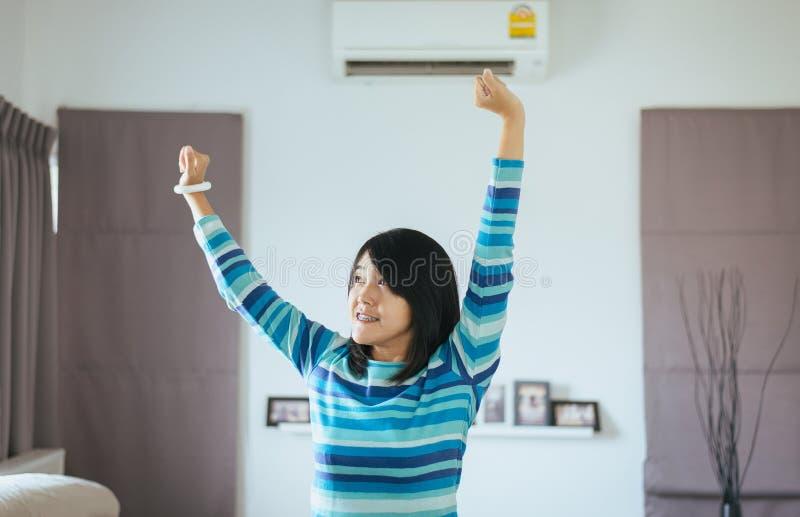 Ευτυχή φρέσκα χέρια γυναικών επάνω και στεμένος στην μπροστινή μετατροπή του κλιματιστικού μηχανήματος στοκ εικόνες