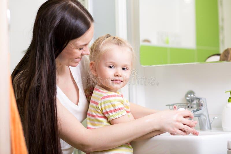 Ευτυχή χέρια πλύσης μητέρων και κορών στο σπίτι στο λουτρό στοκ εικόνες με δικαίωμα ελεύθερης χρήσης