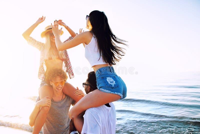 Ευτυχή χαμογελώντας ζεύγη που παίζουν στην παραλία στοκ εικόνα