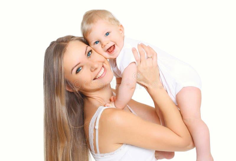 Ευτυχή χαμογελώντας μητέρα και μωρό που έχουν τη διασκέδαση μαζί στο λευκό στοκ φωτογραφία
