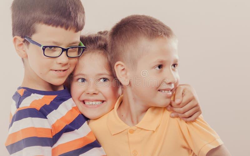 Ευτυχή χαμογελώντας χαριτωμένα μικρό κορίτσι και αγόρια παιδιών στοκ εικόνα