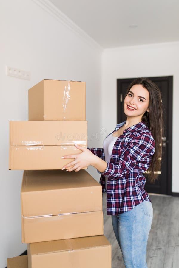 Ευτυχή χαμόγελου κιβώτια χαρτοκιβωτίων γυναικών φέρνοντας που κινούνται στο νέο διαμέρισμα στοκ φωτογραφία με δικαίωμα ελεύθερης χρήσης