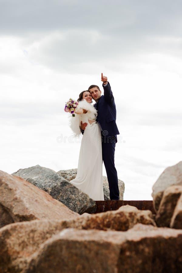 Ευτυχή newlyweds που στέκονται μεταξύ των βράχων στην παραλία. στοκ εικόνα