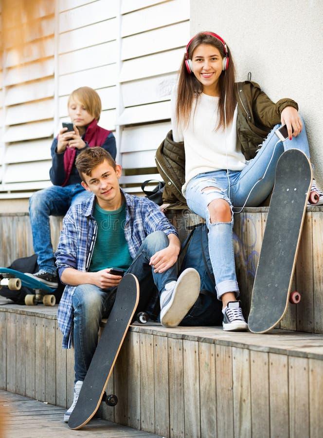 Ευτυχή teens που παίζουν στα smarthphones και που ακούνε τη μουσική στοκ φωτογραφία