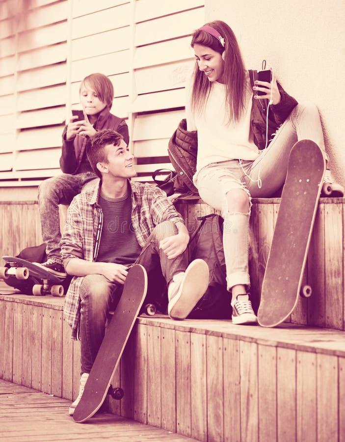 Ευτυχή teens που παίζουν στα smarthphones και που ακούνε τη μουσική στοκ εικόνα