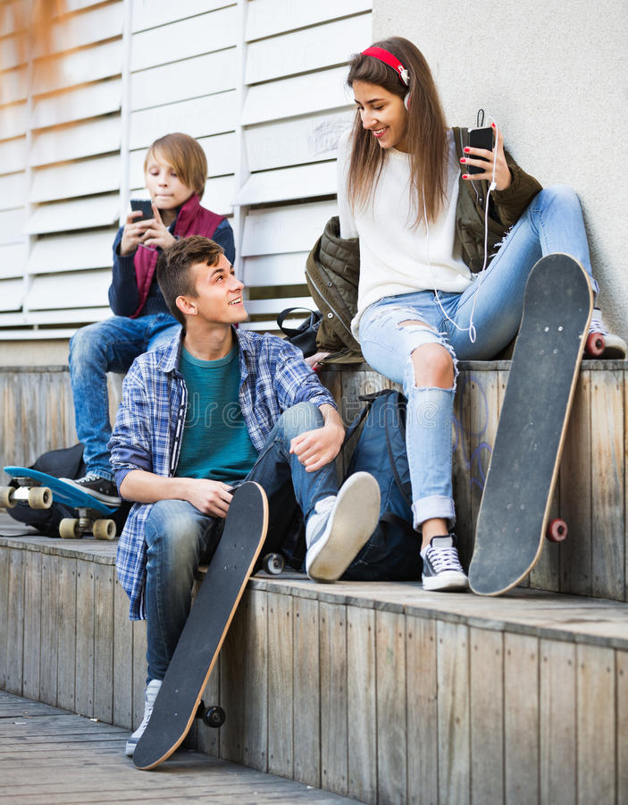 Ευτυχή teens που παίζουν στα smarthphones και που ακούνε τη μουσική στοκ εικόνες με δικαίωμα ελεύθερης χρήσης