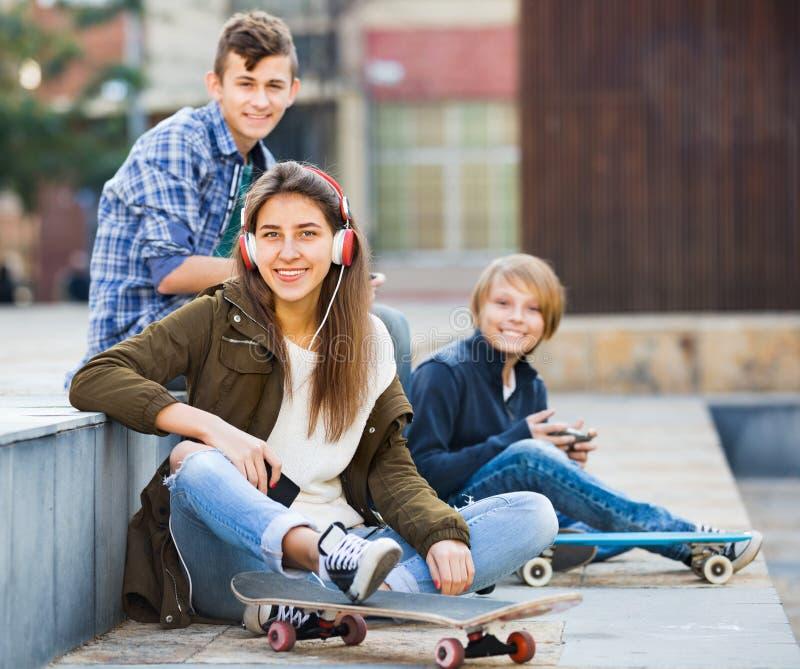 Ευτυχή teens που παίζουν στα smarthphones και που ακούνε τη μουσική στοκ εικόνες