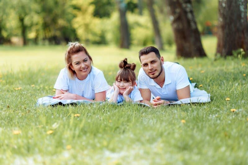 Ευτυχία και αρμονία στη οικογενειακή ζωή r Νέοι μητέρα και πατέρας με την κόρη τους στο πάρκο Ευτυχής οικογένεια στοκ φωτογραφία με δικαίωμα ελεύθερης χρήσης