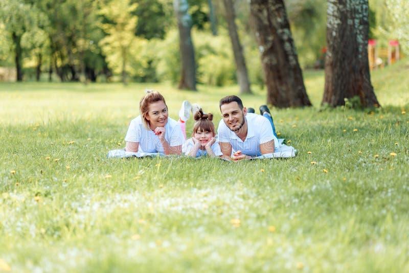 Ευτυχία και αρμονία στη οικογενειακή ζωή r Νέοι μητέρα και πατέρας με την κόρη τους στο πάρκο Ευτυχής οικογένεια στοκ εικόνα με δικαίωμα ελεύθερης χρήσης