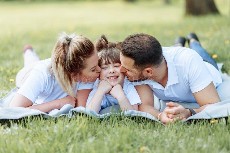 Ευτυχία και αρμονία στη οικογενειακή ζωή r Νέοι μητέρα και πατέρας με την κόρη τους στο πάρκο Ευτυχής οικογένεια στοκ φωτογραφία