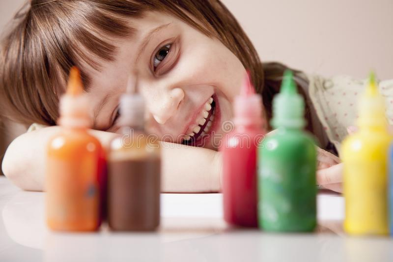 Ευτυχία του παιδιού Λίγο χαριτωμένο κορίτσι που γελά και που κοιτάζει έξω για τα χρωματισμένα χρώματα στοκ εικόνα