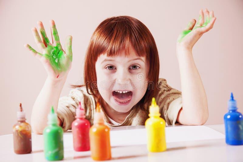 Ευτυχία του παιδιού Λίγο χαριτωμένο κορίτσι που γελά και που χρωματίζει στοκ εικόνα