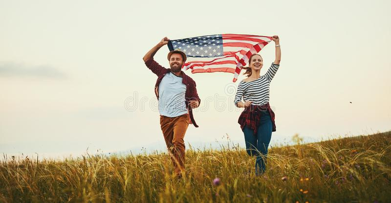 Ευτυχείς άνδρας και γυναίκα ζευγών με τη σημαία των Ηνωμένων Πολιτειών που απολαμβάνουν ηλιοβασίλεμα στη φύση στοκ εικόνες