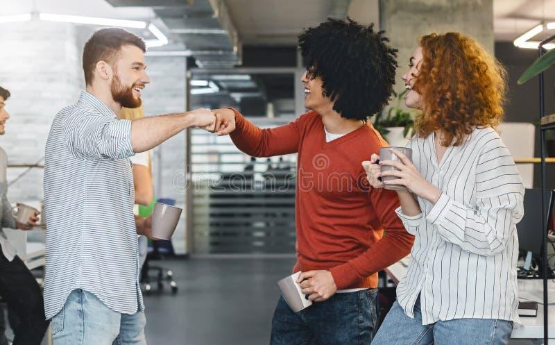 Ευτυχείς άνδρες συνάδελφοι που δίνουν την πρόσκρουση πυγμών κατά τη διάρκεια του διαλείμματος στοκ εικόνες