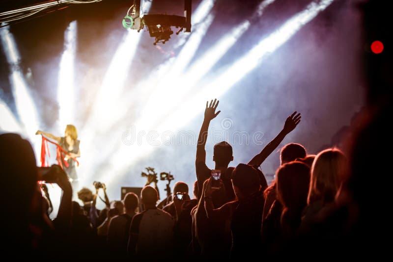Ευτυχείς άνθρωποι που απολαμβάνουν τη συναυλία βράχου, που αυξάνεται επάνω στα χέρια και το χτύπημα της ευχαρίστησης στοκ εικόνες