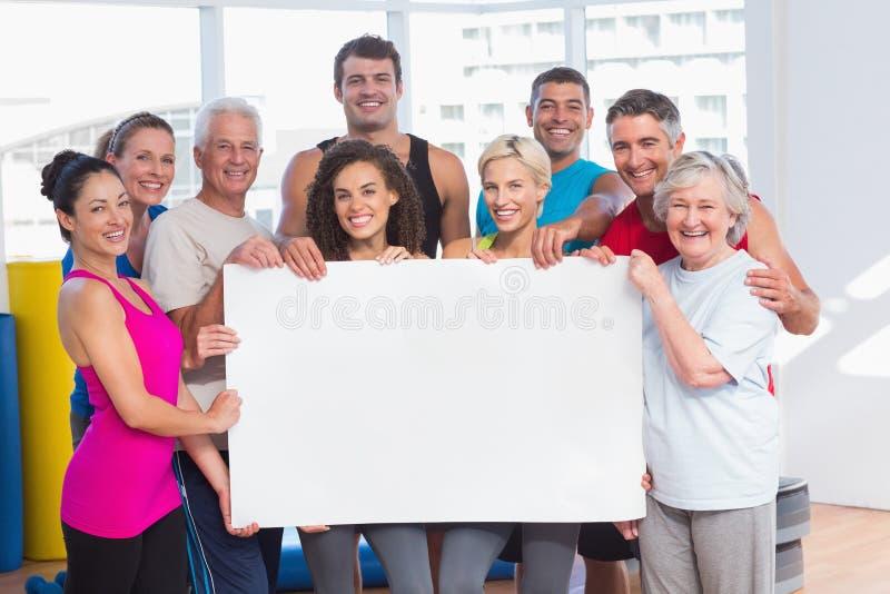 Ευτυχείς άνθρωποι που κρατούν τον κενό πίνακα διαφημίσεων στη λέσχη υγείας στοκ εικόνες