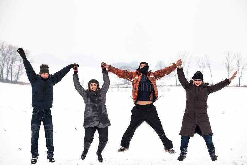 Ευτυχείς άνθρωποι που πηδούν το χειμώνα χιονιού στοκ φωτογραφία με δικαίωμα ελεύθερης χρήσης