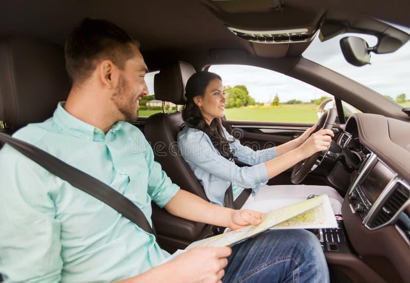 Ευτυχείς άνδρας και γυναίκα με την οδήγηση οδικών χαρτών στο αυτοκίνητο στοκ εικόνες